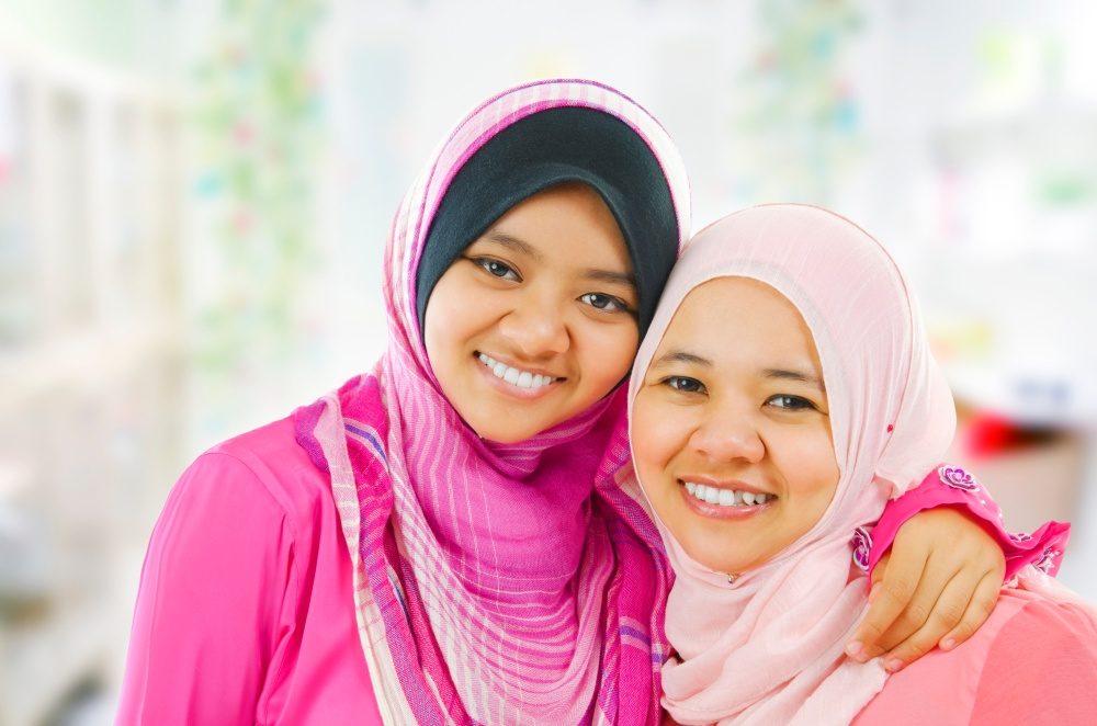 happy muslim women wearing hijabs, embracing each other while looking at camera.